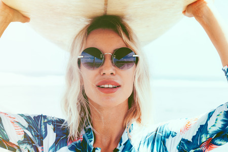 Foto de Surfer girl in sport swimwear and sunglasses posing with surfboard on the beach. Active lifestyle and summer vacations. - Imagen libre de derechos