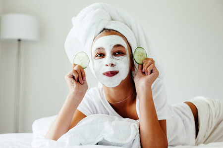Photo pour 10 years old preteen chilling in the bedroom and making clay facial mask. Teenage girl doing anti blemish skin treatment. Morning skin care routine. - image libre de droit
