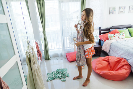 Foto de 10 years old pre teen girl choosing outfit in her closet. Messy in the bedroom, clotning on the floor. Teenager is dressing up and singing in the morning. - Imagen libre de derechos