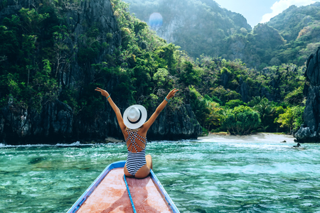 Photo pour Back view of the young woman in hat relaxing on the boat and looking at the island. Travelling tour in Asia: El Nido, Palawan, Philippines. - image libre de droit