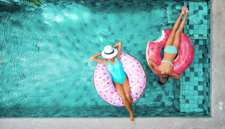 Photo for Two people (mom and child) relaxing on donut lilo in the pool at private villa. Summer holiday idyllic. High view from above. - Royalty Free Image