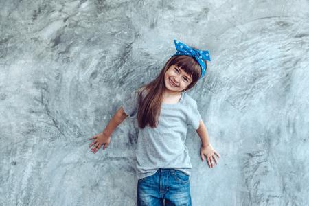 Foto de Fashion child wearing blank gray t-shirt and jeans posing against rough concgrete wall, minimalist street fashion kids style - Imagen libre de derechos