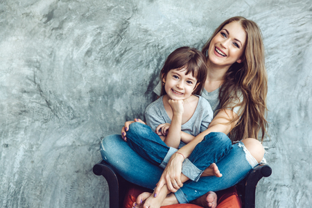 Photo pour Young beautiful mom with her daughter wearing blank gray t-shirt and jeans posing against rough concgrete wall, minimalist street fashion style, family same look, clothing for parent and child. - image libre de droit