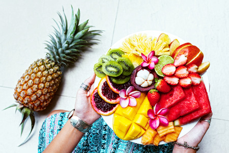 Foto de Hands holding served fruit plate, top view from above. Exotic summer diet. Tropical beach lifestyle. - Imagen libre de derechos