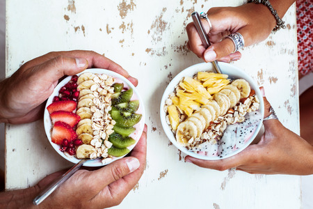 Foto de Smoothie bowls with mixed tropical fresh fruits on wooden table with hands, top view from above. Summer healthy diet, vegan breakfast. - Imagen libre de derechos