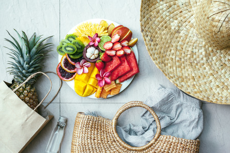Photo pour Fresh fruit plate and set of summer fashion beach accessories, top view from above (overhead). Tropical beach lifestyle. - image libre de droit