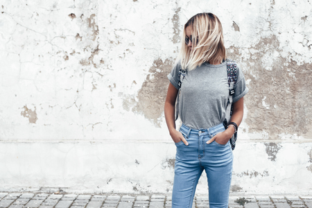 Photo for Hipster girl wearing blank gray t-shirt, jeans and backpack posing against rough street wall, minimalist urban clothing style, mockup for tshirt print store - Royalty Free Image