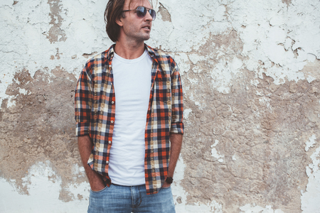 Foto de Handsome man wearing blank tshirt posing against street wall, front t shirt mock up on model, fashion urban style - Imagen libre de derechos
