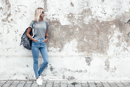 Foto de Hipster girl wearing blank gray t-shirt, jeans and backpack posing against rough street wall, minimalist urban clothing style, mockup for tshirt print store - Imagen libre de derechos