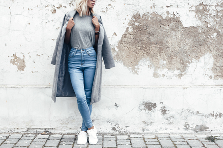 Photo pour Hipster girl wearing blank gray t-shirt, jeans and coat posing against rough street wall, minimalist urban clothing style, mockup for tshirt print store - image libre de droit
