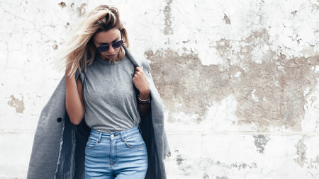 Foto de Hipster girl wearing blank gray t-shirt, jeans and coat posing against rough street wall, minimalist urban clothing style, mock up for tshirt print store - Imagen libre de derechos