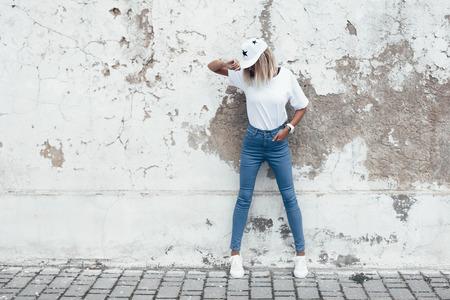 Foto de Hipster girl wearing blank white t-shirt, jeans and baseball cap posing against rough street wall, full length portrait, minimalist urban clothing style, mockup for tshirt print store - Imagen libre de derechos