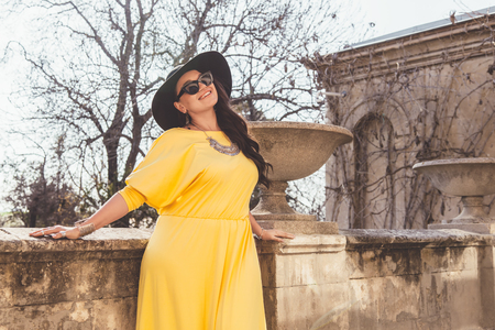 Photo pour Young stylish woman wearing yellow maxi dress, black hat and sunglasses walking in the city street. Spring fashion outfit, elegant look. Plus size model. - image libre de droit