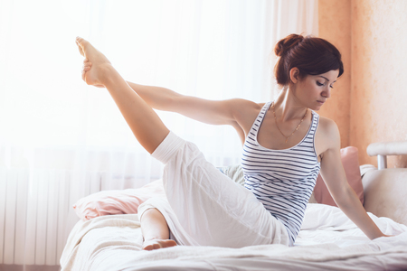 Foto de Woman doing yoga exercise on bed at home. Morning workout in bedroom. Healthy and sport lifestyle. - Imagen libre de derechos