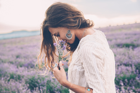 Foto de Beautiful model walking in spring or summer lavender field in sunrise backlit. Boho style clothing and jewelry. - Imagen libre de derechos