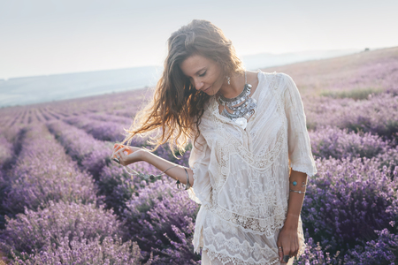 Photo pour Beautiful model walking in spring or summer lavender field in sunrise backlit. Boho style clothing and jewelry. - image libre de droit