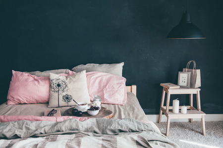 Photo for Black and pink stylish loft bedroom. Unmade bed with breakfast and reading on tray. Lamp and interior decor over blank blackboard wall with copyspace. Cozy modern living space. - Royalty Free Image