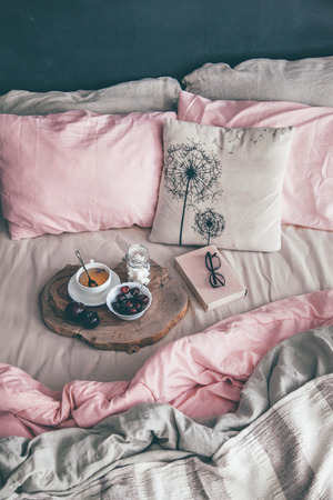 Photo pour Black loft bedroom and pastel bedding set. Unmade bed with breakfast and reading on tray. Interior decor over blackboard wall. Cozy modern living space. - image libre de droit
