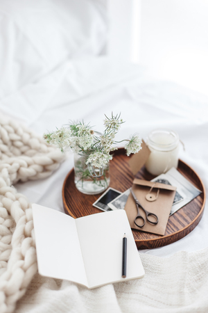Foto de Wooden tray with paper notebook, old photos, candle and spring flowers on white bedding. Relaxing, or working, or writing diary or blog in bed at home. - Imagen libre de derechos