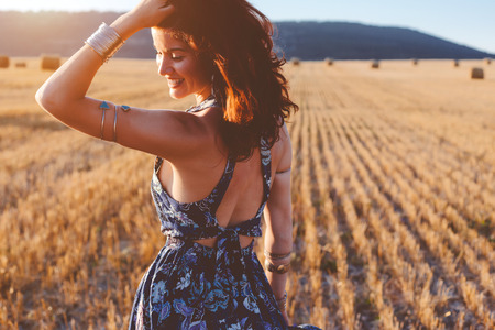 Foto de Beautiful model wearing summer cotton maxi dress and bracelets posing in autumn field with hay stack. Boho style clothing and jewelry. - Imagen libre de derechos