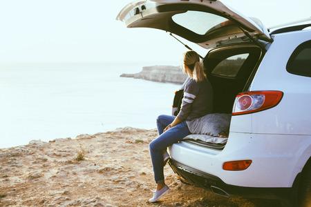 Foto de Woman relaxing inside car trunk and watching on sea. Fall trip in sunset. Freedom travel concept. Autumn weekend. - Imagen libre de derechos