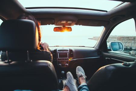 Foto de Fall car trip in sunset. Freedom travel concept. Spending weekend in roadtrip. Woman feet on car dashboard. - Imagen libre de derechos