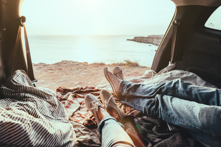 Foto de Man and woman relaxing inside trunk and watching at the sea. Fall car trip in sunset. Freedom travel concept. Autumn weekend. - Imagen libre de derechos