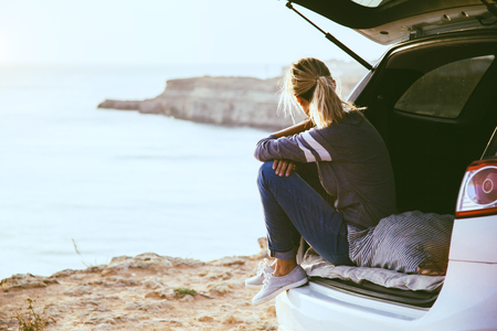 Photo for Woman relaxing inside car trunk and watching on sea. Fall trip in sunset. Freedom travel concept. Autumn weekend. - Royalty Free Image