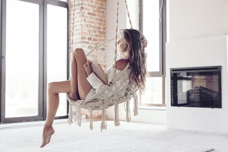 Photo pour Young woman chilling at home in comfortable hanging chair near fireplace. Girl relaxing and reading book in swing in loft living room with brick walls. - image libre de droit