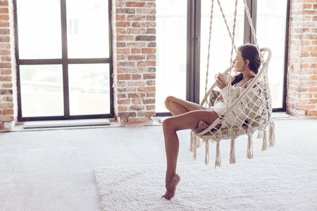 Foto de Young woman chilling at home in comfortable hanging chair in front of big window. Girl relaxing in swing in loft living room with brick walls. Beautiful legs barefoot on white carpet. - Imagen libre de derechos