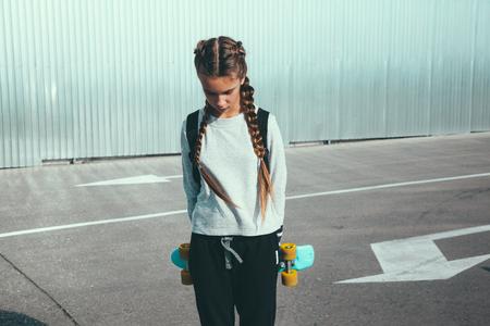 Foto de 11-12 years old tween girl wearing fashion sportswear rollerskating on skateboard in the city street, urban hipster style - Imagen libre de derechos