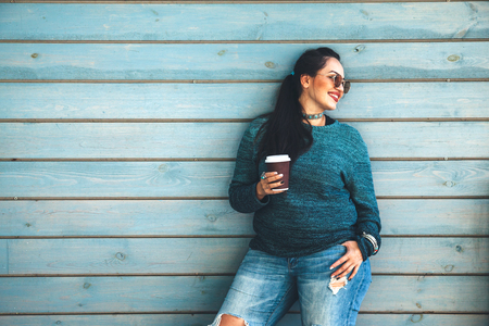 Photo pour Beautiful woman wearing fall sweater, ripped jeans and glasses drinking take away coffee standing against cafe wall on city street. Casual fashion, elegant everyday look. Plus size model. - image libre de droit