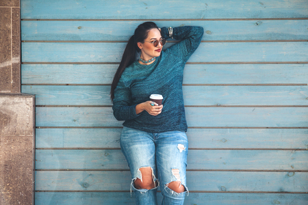 Photo pour Beautiful woman wearing drinking take away coffee standing against cafe wall on city street. - image libre de droit