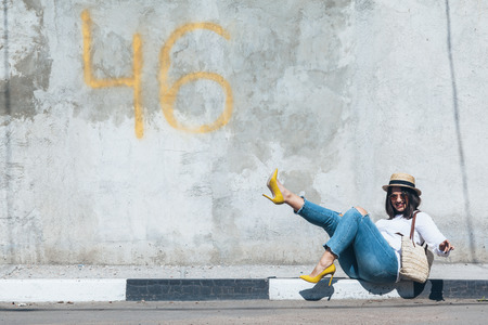 Foto de Young fashion woman wearing ripped jeans, colorful heel shoes and straw accessories posing over gray concrete city wall. Plus size model. - Imagen libre de derechos