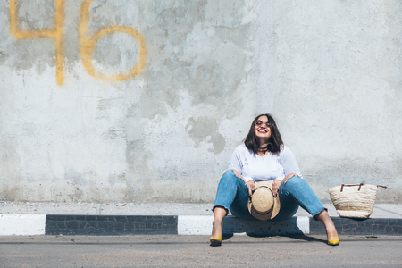 Foto de Young fashion woman wearing ripped jeans, colorful heels and straw accessories posing over gray concrete city wall. Plus size model. - Imagen libre de derechos