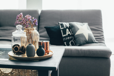 Foto de Home interior decor in gray and brown colors: glass jar with dried flowers, vase and candle on the wooden tray on the coffee table over sofa with cushions. Living room decoration. - Imagen libre de derechos