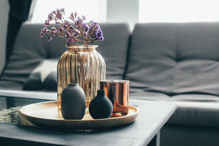 Photo pour Home interior decor in gray and brown colors: glass jar with dried flowers, vase and candle on the wooden tray on the coffee table over sofa. Living room decoration. - image libre de droit