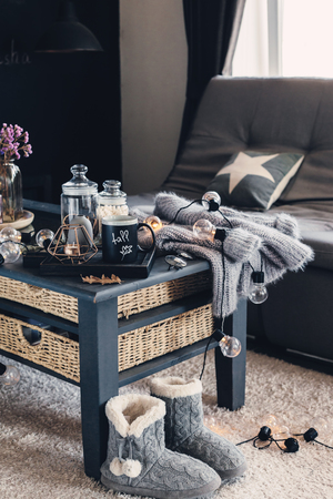 Photo pour Still life details of living room interior. Cup of coffee on rustic wooden tray, candle and warm woolen sweater on table, decorated with led lights. Autumn weekend concept. Fall home decoration. - image libre de droit