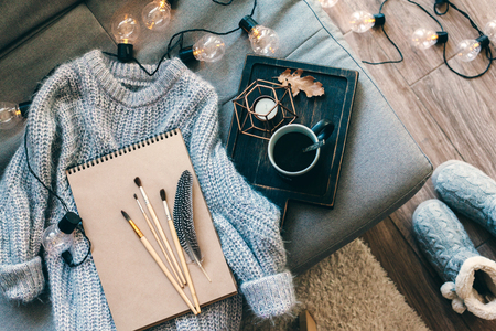Foto de Still life details. Cup of coffee on rustic wooden tray, sketchbook and warm woolen sweater on sofa, decorated with led lights, top view point. Autumn weekend concept. Hobby and crafts. - Imagen libre de derechos