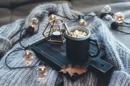 Photo for Still life details of living room. Cup of coffee on rustic wooden tray, candle and warm woolen sweater on sofa, decorated with led lights. Autumn weekend concept. Fall home decoration. - Royalty Free Image