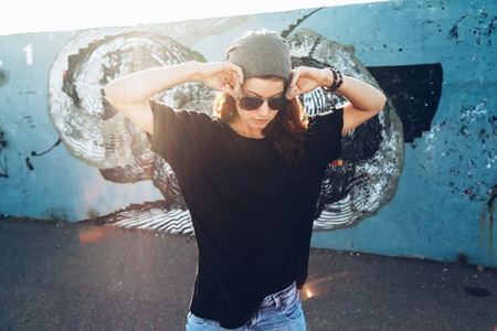 Foto de Model wearing plain black t-shirt and hipster sunglasses posing against street wall, teen urban clothing style, mockup for tshirt print store - Imagen libre de derechos