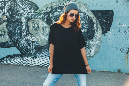 Photo for Model wearing plain black t-shirt and hipster sunglasses posing against street wall, teen urban clothing style, mockup for tshirt print store - Royalty Free Image