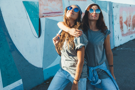 Foto de Two models wearing plain gray t-shirts and hipster sunglasses posing against street wall. Teen urban clothing style, same look. Mockup for tshirt print store. - Imagen libre de derechos