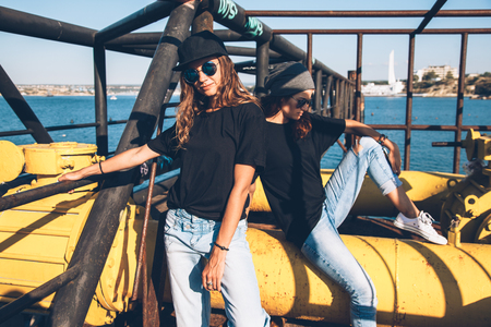 Foto de Two model wearing plain black t-shirt and hipster sunglasses, teen urban clothing style, mockup for tshirt print store - Imagen libre de derechos
