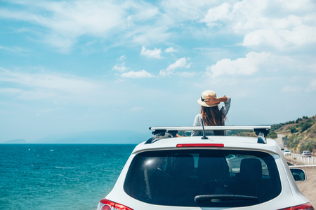 Foto de Rear view of pre teen child in car over sea view on summer roadtrip to the beach - Imagen libre de derechos