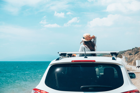 Photo pour Rear view of pre teen child in car over sea view on summer roadtrip to the beach - image libre de droit