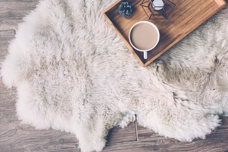 Foto de Mug with coffee and home decor on wooden serving tray on sheep skin rug. Winter weekend concept, top view - Imagen libre de derechos