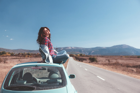 Foto de Hipster girl relaxing on the car roof in her autumn road trip, carefree and enjoying freedom and travel. Wanderlust concept scene. - Imagen libre de derechos