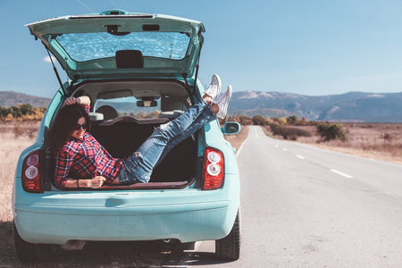 Foto de Hipster girl relaxing in the car trunk in her autumn road trip, carefree and enjoying freedom and travel. Wanderlust concept scene. - Imagen libre de derechos