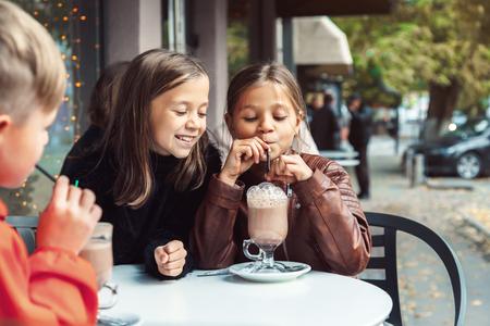 Foto de Children having fun in outdoor cafe. Kids talking and drinking cocoa for the breakfast in the city street in autumn. Spending weekend with friends. - Imagen libre de derechos
